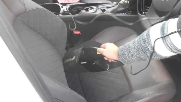 車のシートを車用掃除機で掃除する男性