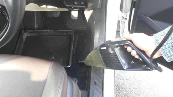 車内マットを車用掃除機で掃除する男性
