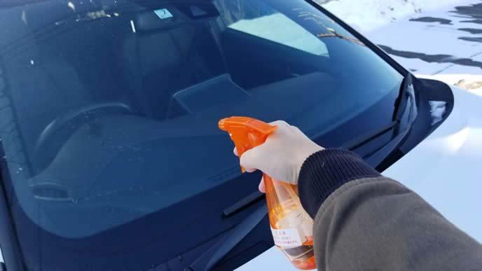 車に解氷スプレーを使う男性
